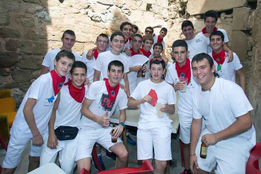 Jóvenes que combaten con bebida fresca y abanicos las temperaturas veraniegas durante las fiestas de Arróniz.