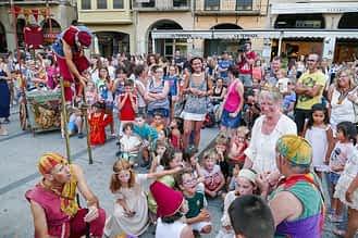 Niños y adultos disfrutando con uno de los grupos teatrales en la plaza de los Fueros.