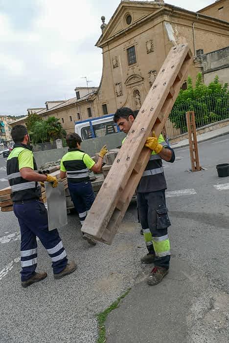 Un empleado portando un tablón del vallado.