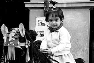 1968. Ana Mañeru Sesma, montada en un caballito en la plaza de los Fueros.