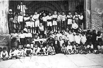 Década de 1920. En el centro, de pie y con camisa oscura y brazos en jarra, Paco Foti, con niños y niñas de su edad en el pórtico de la iglesia de San Juan.
