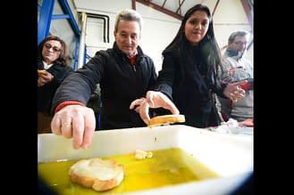 El trujal acogió la degustación. Los asistentes no dudaron en untar el pan en las bandejas de aceite.