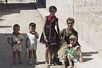 Fiestas de 1962. José Mª y Pedro Mª Mañeru, Begoña Astarriaga con la abuela Dolores Belda y Loli Mañeru. Sostienen a una oveja para la fotografía.